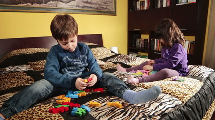 two children playing with puzzle