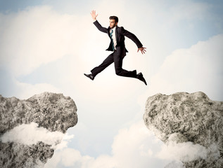 Happy business man jumping over a cliff