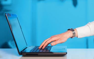 Businessman pressing modern laptop computer on colorful backgrou