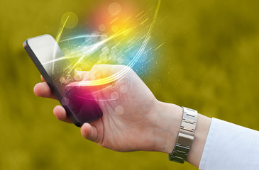 Hand holding smart phone with abstract glowing lines