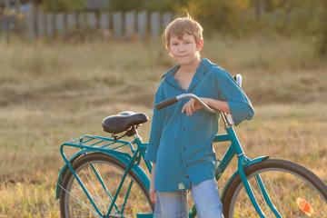 Portrait of teenager with blue bike in farm field