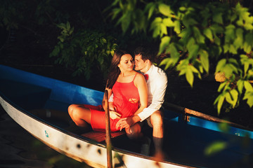 Sensual couple in a boat sits in a boat at sunset