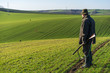 Leinwanddruck Bild - Gamekeeper walks over field.