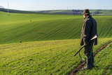 Gamekeeper walks over field.