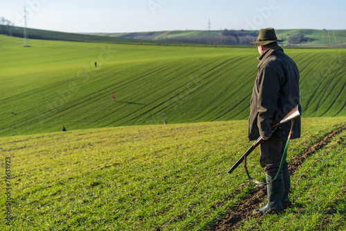 Gamekeeper walks over field. - 76631923