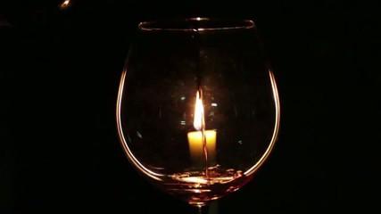 Bicchiere con candela e vino versato