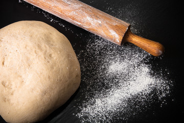 Dough, rolling pin and flour on a black background