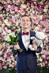 Young funny groom with bouquet and toy on the flowers wall bac