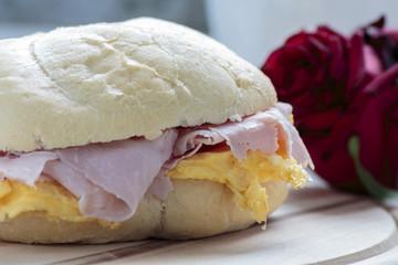 Ham & eggs sandwich on wooden board