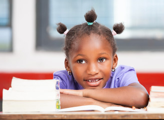 Afroamerican female student laying on the desk among books