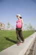 pink pregnant walking at park