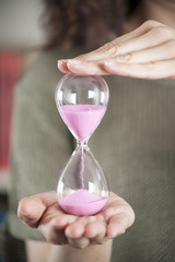 pink sand clock in woman hands