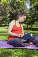 young pregnant reading at park