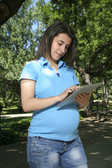 young pregnant touching tablet smiling