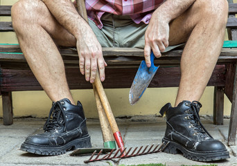 gardener with hairy legs in boots resting on a bench