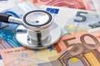 Leinwandbild Motiv Stethoskop auf Euroscheinen