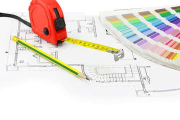 Tape measure, pencil and color sample over a construction plan d
