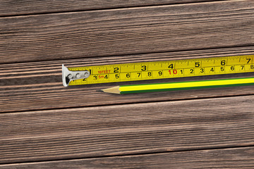 Tape measure and pencil on wooden background