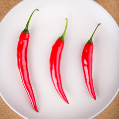 Three fresh chili peppers on plate