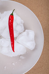 Fresh chili pepper with ice on plate