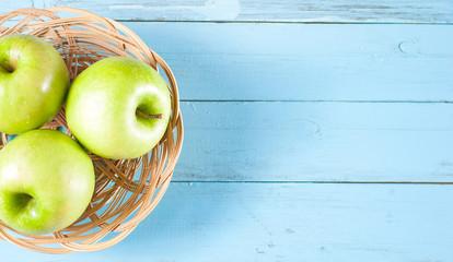 Green apples in basket on blue wood background