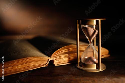 libro antico con clessidra - 76647337
