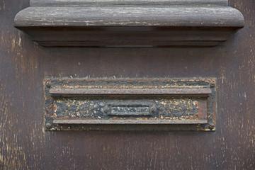 Briefschlitz an einer verwitterten Holztür