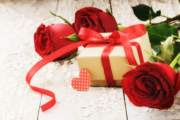 Valentine's setting with bouquet of red roses and present