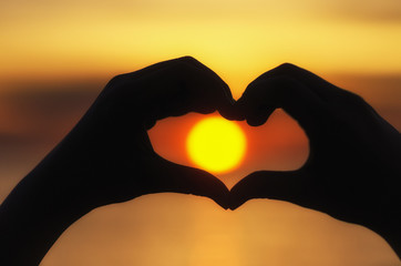 Silhouette of hands in form of heart when sweethearts have touch