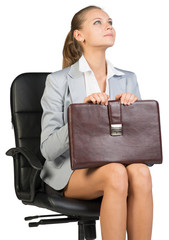 Businesswoman on office chair, holding suitcase