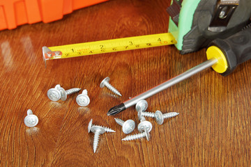 Measure tape and a screwdriver with screws on the wooden table