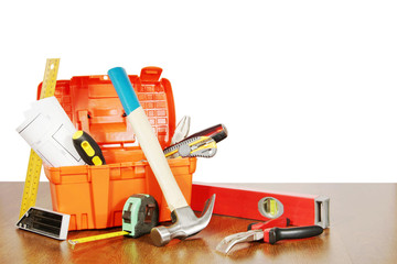 Plastic box with various working tools stands on a wooden table
