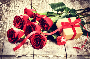 Valentine's setting with bouquet of red roses and present in box