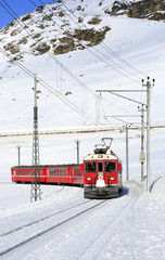 A red swiss train running through the snow, Switzerland.