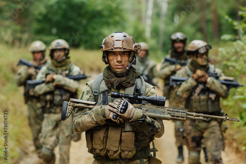 Leinwanddruck Bild sniper stands with arms and looks forward