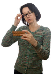 Woman  in  glasses looks at medicament