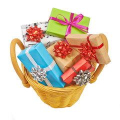 Many colored gift boxes in a basket isolated on white background
