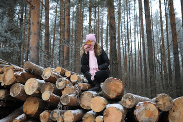 the young woman poses against logs