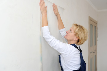 the forewoman glues wall-paper in the room