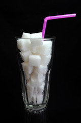 Sugar cubes in glass on black background