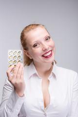 Junge lächelnde Frau mit Tabletten