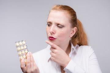 Junge Frau mit Tabletten in der Hand überlegt