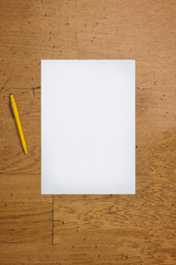 Pen and blank paper sheet on a worn wooden table