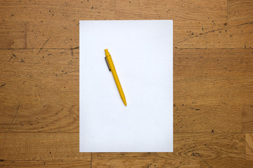 Pen on a blank paper sheet on a worn wooden table