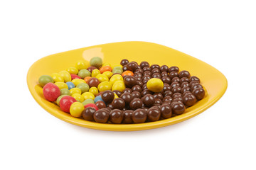 Chocolate balls and multicolored peanut glaze on a yellow plate