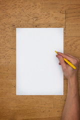 Hand holding pen on blank paper sheet on a table
