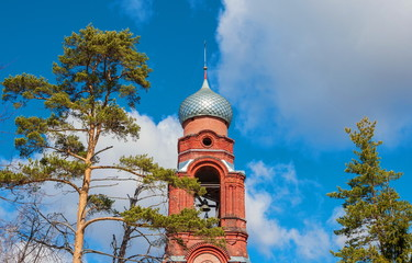 bell tower with bell against the sky in a pine forest