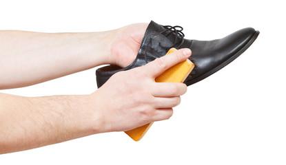 Shoeshiner brushing black shoe by brush