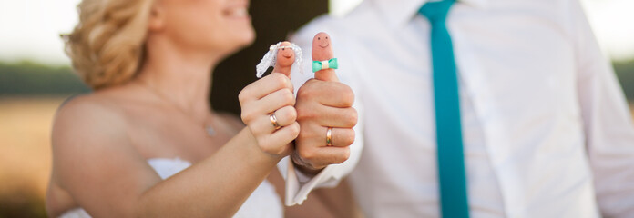 Wedding - couple show fingers dolls decorated as little bride an