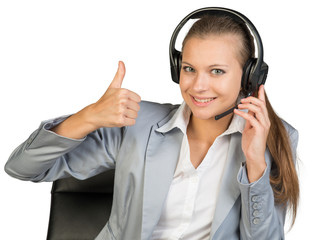 Businesswoman in headset showing thumb up